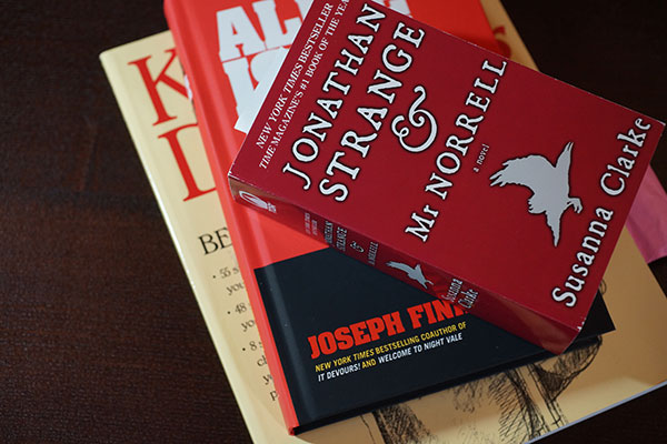 Book pile of Jonathan Strange and Mr. Norrell, Alice Isn't Dead, and Keys to Drawing