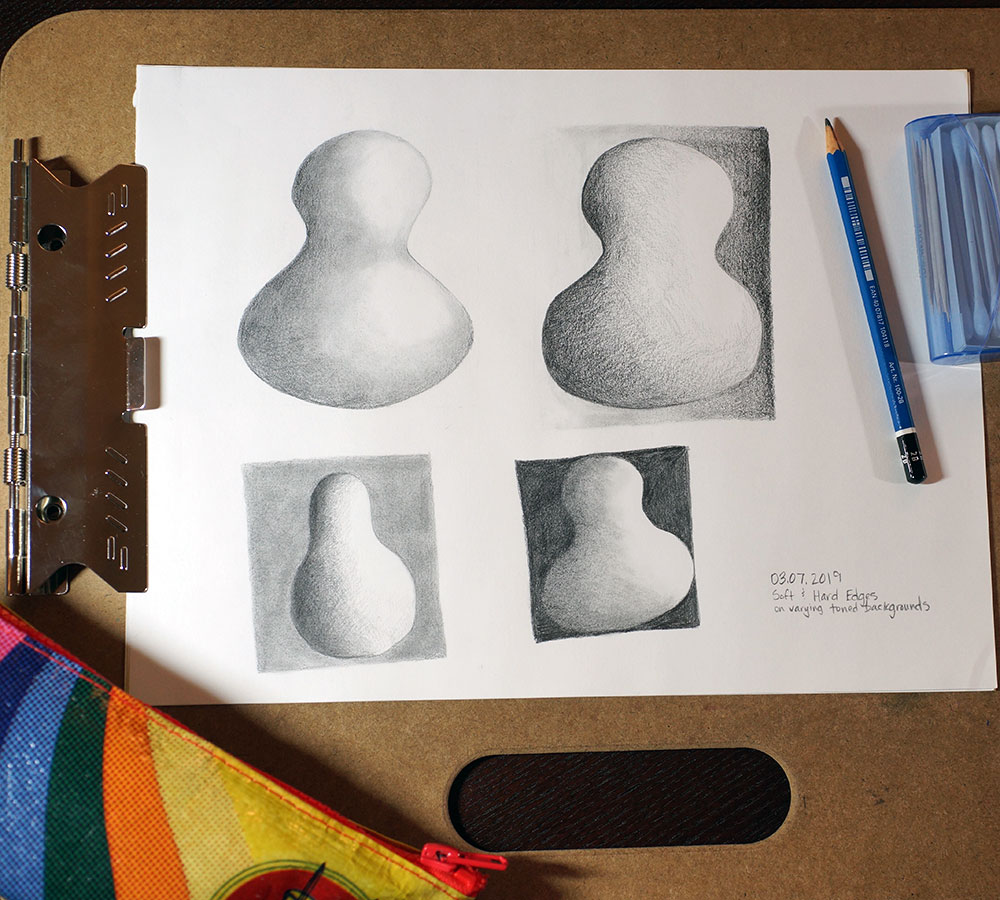 Drawing board with paper cliped to it of soft and hard edge practice.