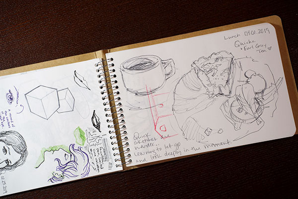 Tan sketchbook open to recent sketches of food and faces