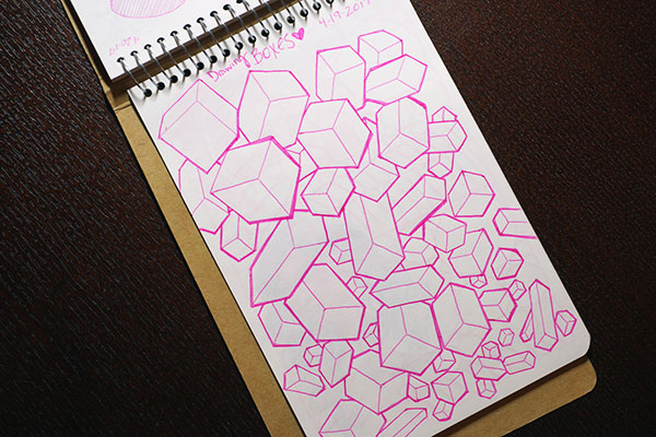 Tan sketchbook open to old sketch of many boxes rotated in space, using pink ink