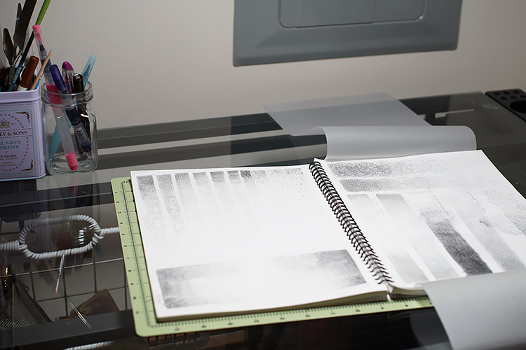An open sketchbook ontop of a drafting table, with drawings of value practice in pencil on the pages