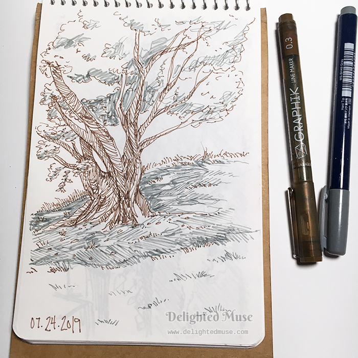 Sketchbook page showing a tree and grass in brown brush pen and black fineliner ink.