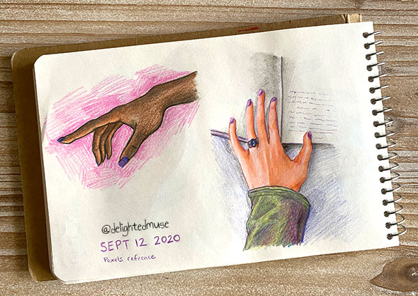 Sketchbook page of two hands studies, one hand pointing to the left, drawn with darker skin tone and purple nail polish. The other hand is resting on a book, this hand with lighter skin and purple nail polish