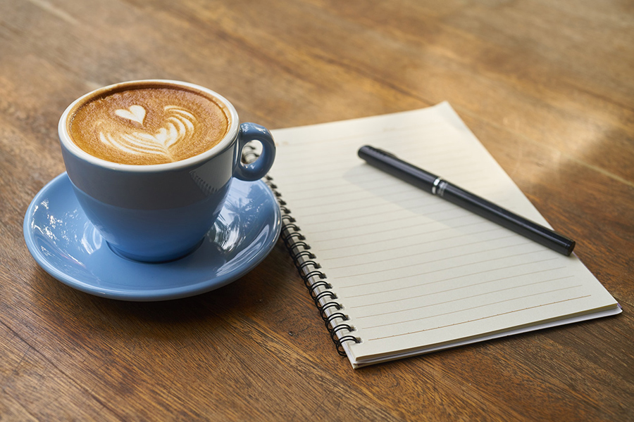 Photo of a blue coffee cup on a saucer beside a notebook
