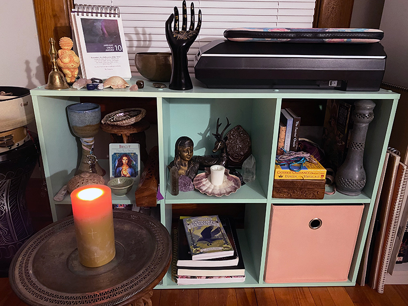A low bookshelf with cube shaped openings, being used as a Wiccan altar, with various decorations, statues, books, and stones.