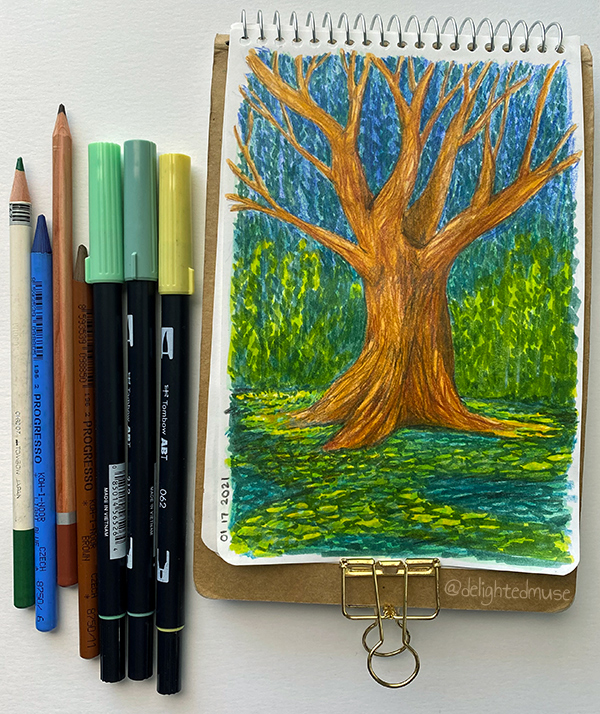 Photo of an open sketchbook with a drawing of a tree with bare limbs, surrounded by impressionistic leaf shapes. To the left of the sketchbook, there are brush pens and pencils that were used in the drawing.
