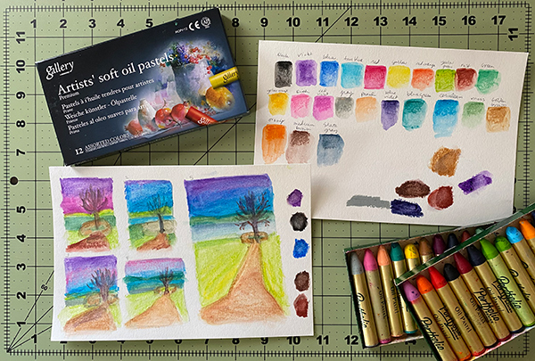 A photo of two sheets of watercolor paper with thumbnail planning sketches on one and color swatches on the other. There are oil pastel boxes above and below the papers.
