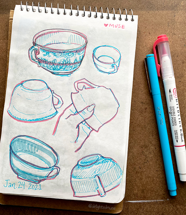 A sketchbook page of a teacup drawn in pink and blue pen