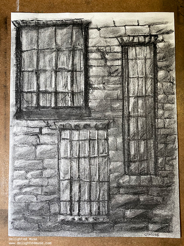 Charcoal drawing with soft, blended marks of a brick wall with three windows