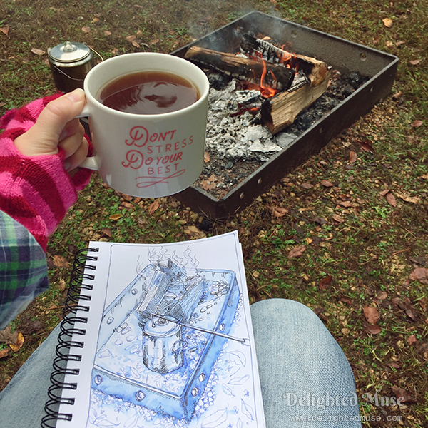 A photo of a woman holding a cup of coffee with a sketchbook on her lap. The darwing is of the firepit and percolator in front of her.
