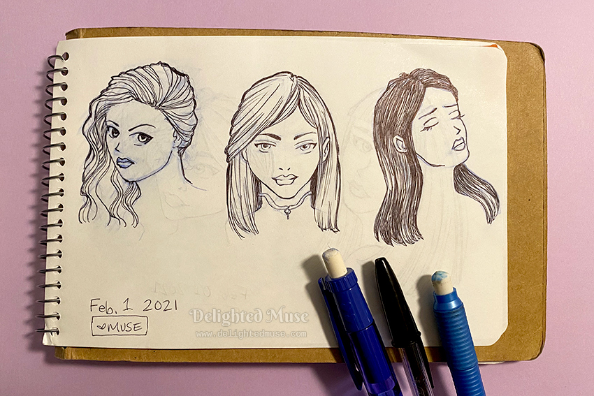 A sketchbook page with a drawing of three faces.