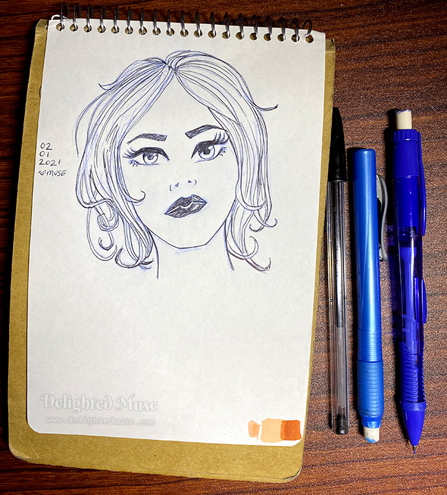 A sketchbook page with a drawing of a woman's face