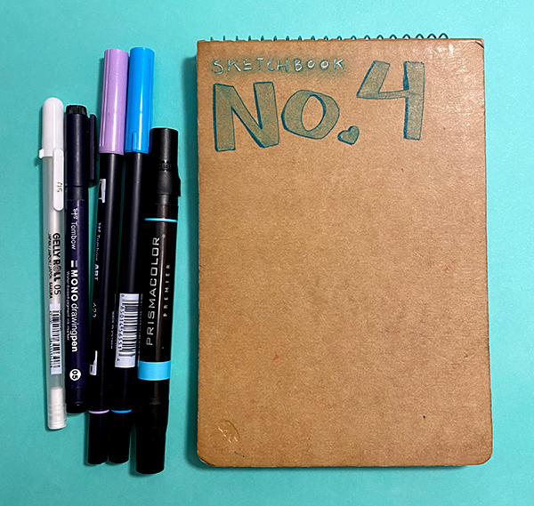 Photo of a sketchbook, with markers and pens next to the sketchbook