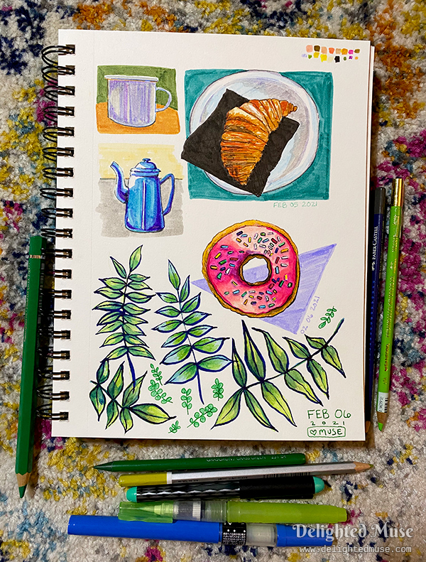 Sketchbook page filled with drawings of a donut, leaves, a teapot, a croissant, and a mug. Watercolor pencils and ink pens are laid next to the sketchbook