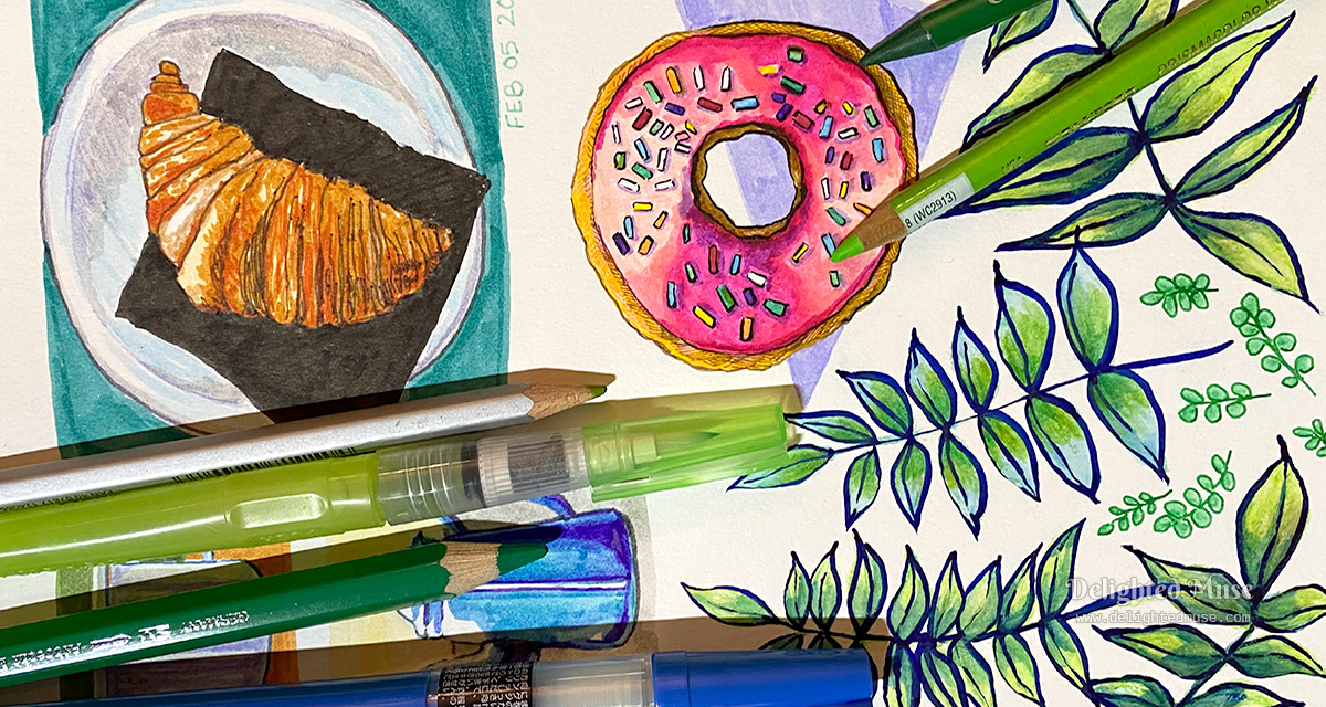 Sketchbook page showing drawings of a croissant, donut and leaves. Laid ontop are watercolor pencils, a water brush, and an ink brush.