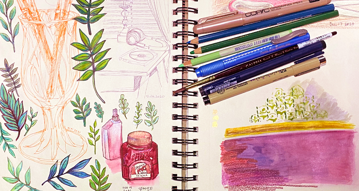 An open sketchbook with drawings of leaves and still life studies, pens and pencils are piles ontop of the right page