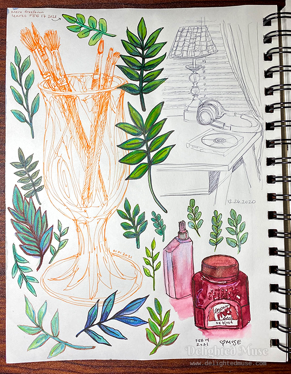 Sketchbook page showing a still life of a cup with paint brushes, a table with a lamp, ink bottles, and leaves