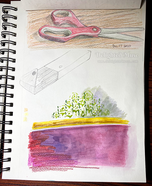 A sketchbook page with a colored pencil drawing of scissors, a pencil box, and some color blending swatches