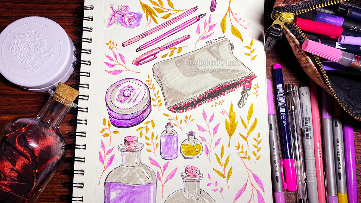 A sketchbook page with marker and fineliner pen drawings of potion bottles, leaves, a zippered pouch, markers, and a lotion tin. Drawing materials are piled to the right of the sketchbook.
