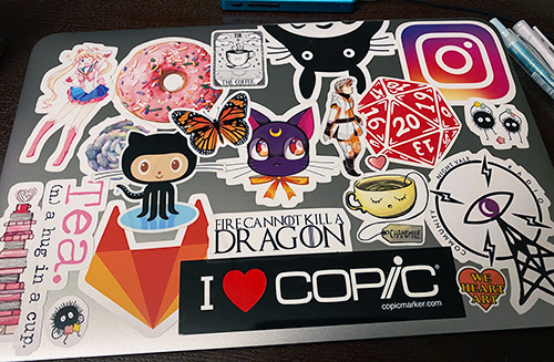 A closed laptop covered in many different stickers, some Sailor Moon fan art, a donut, a 20-sided die, Totoro, GitLab and GitHub mascots, and others.