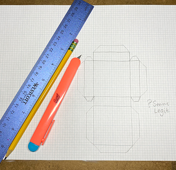 A sheet of graph paper with a drawing of a box cut out. A ruler, pencil, and craft knife sit on top. The paper has the text Seems Legit