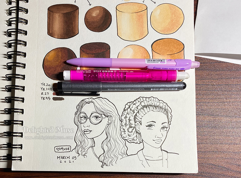 A sketchbook page with the line art of two female faces drawn in black ink