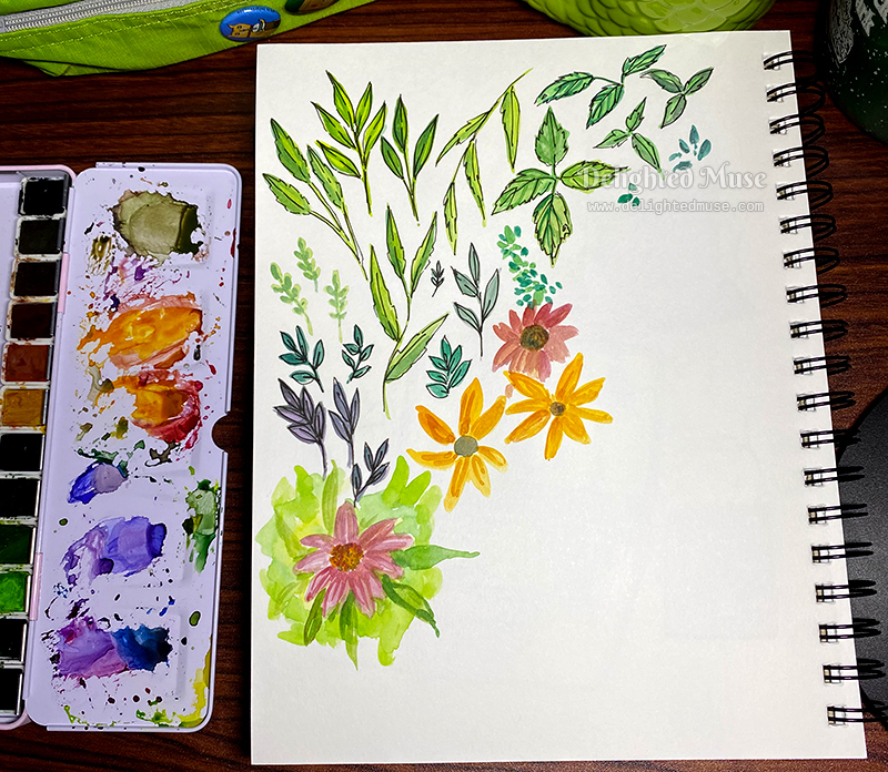 A sketchbook page with paintings of leaves and flowers. To the left is an open watercolor pan set.