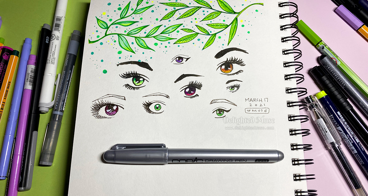 Sketchbook page with drawings of bright green branches of leaves and stylized eyes. Piles of markers and pens are laid on either side of the sketchbook.